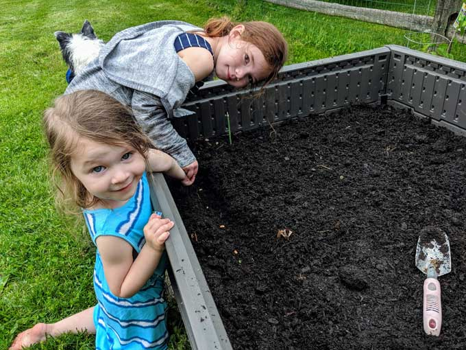 Planting with Kids - children and gardening fun filling a raised bed with soil