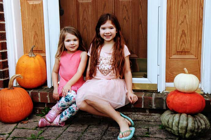 Sisters sitting on front step with beautiful colorful stacking pumpkins and orange jack-o-lantern pumpkins