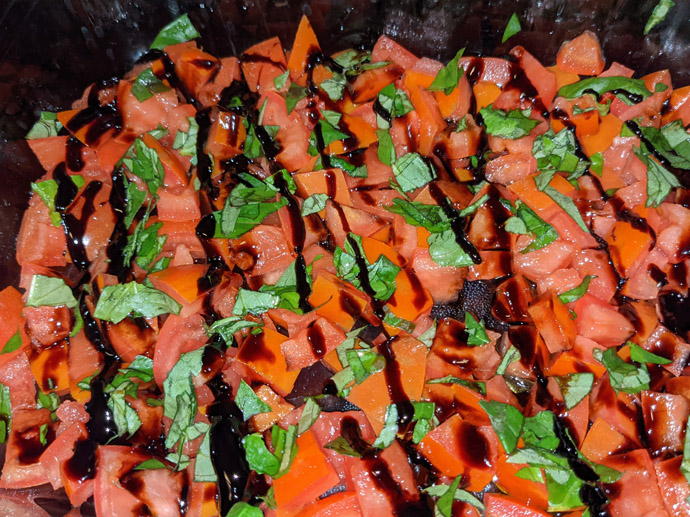 Balsamic Glaze on Roma Tomatoes and Fresh Basil Leaves in a Glass Pan