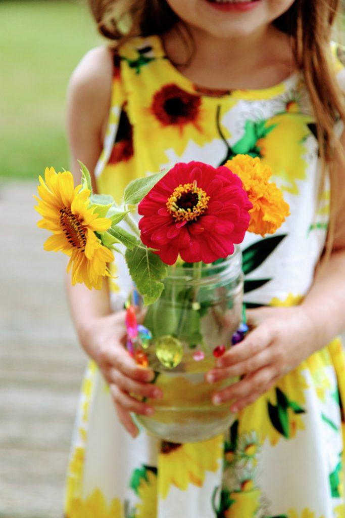 Little Daughter Holding Vase of Fresh Cut Flowers including Dwarf Sunflower Sunspot