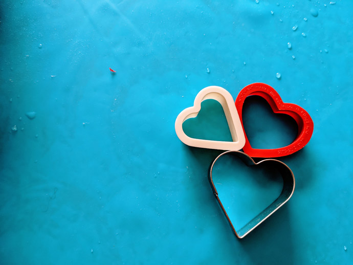 Trio of Heart Shaped Cookie Cutters on a Blue Background