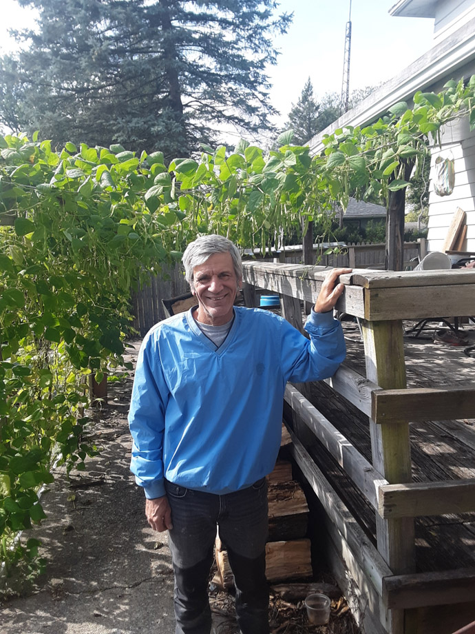 Paul DeRose the Pool Gardener under the green beans by his deck, Photo Courtesy of ThePoolGardener.com