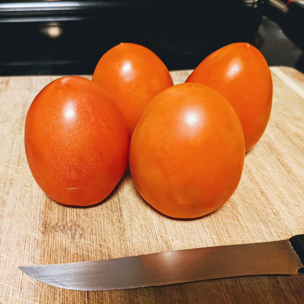 Plum Tomatoes Fresh and Ripe on a cutting Board with a Knife