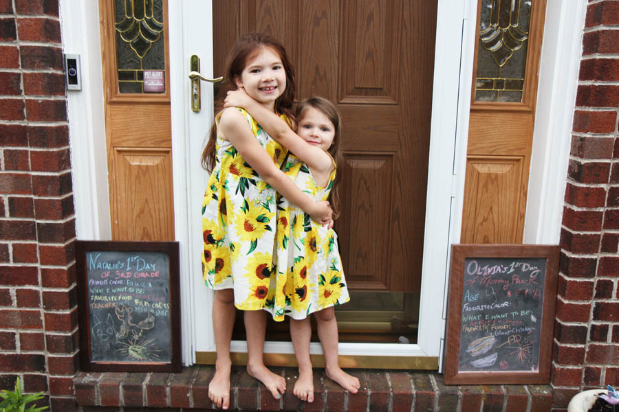 Sisters in Sunflower Dresses on the First Day of School with their Chalkboards at the Front Door