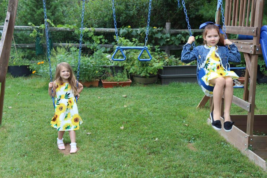 Girls in sunflower dresses on swing set by raised garden beds