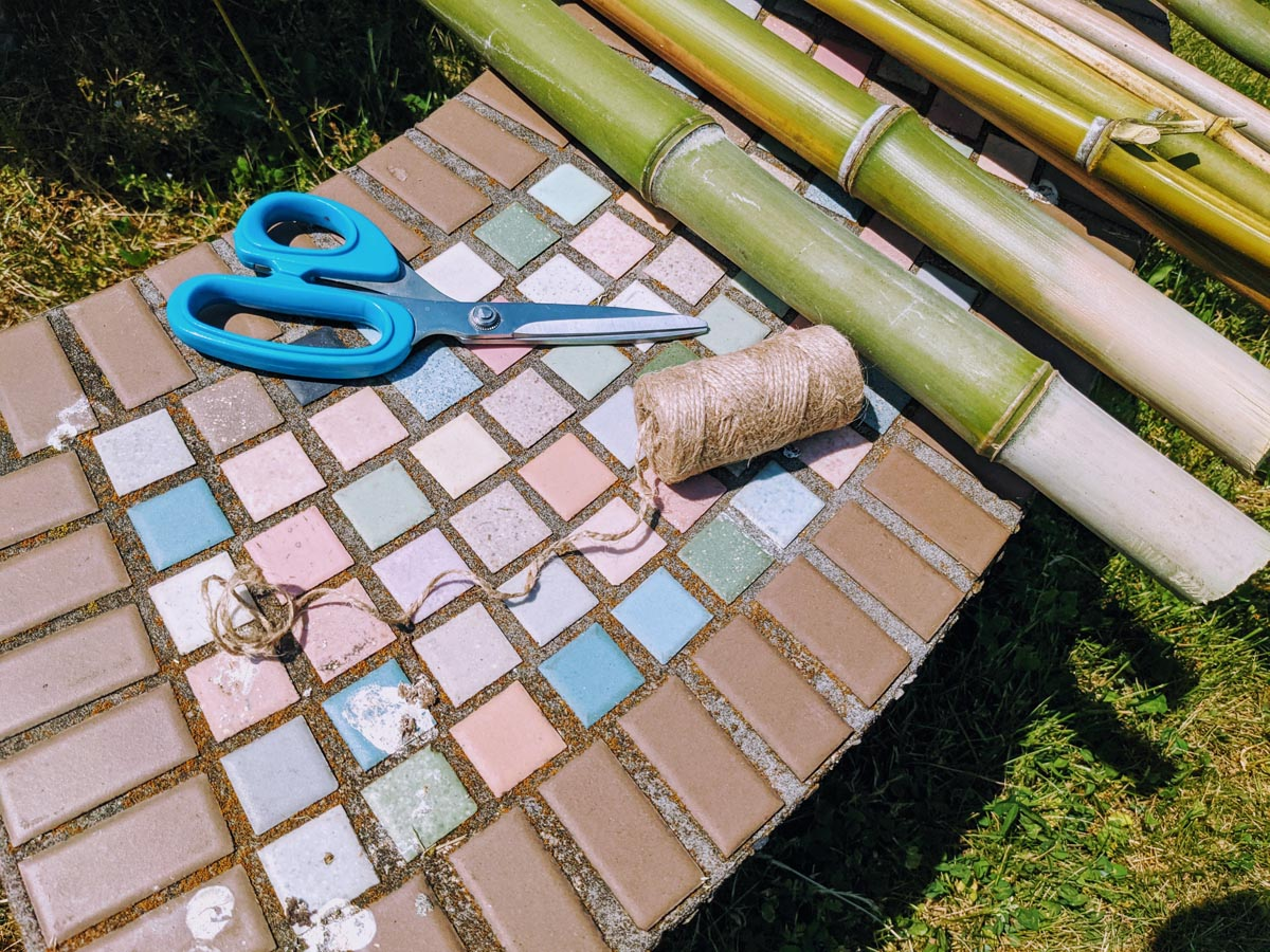 Green Bean Teepee supplies - scissors, bamboo and twine on a mosaic tile bench