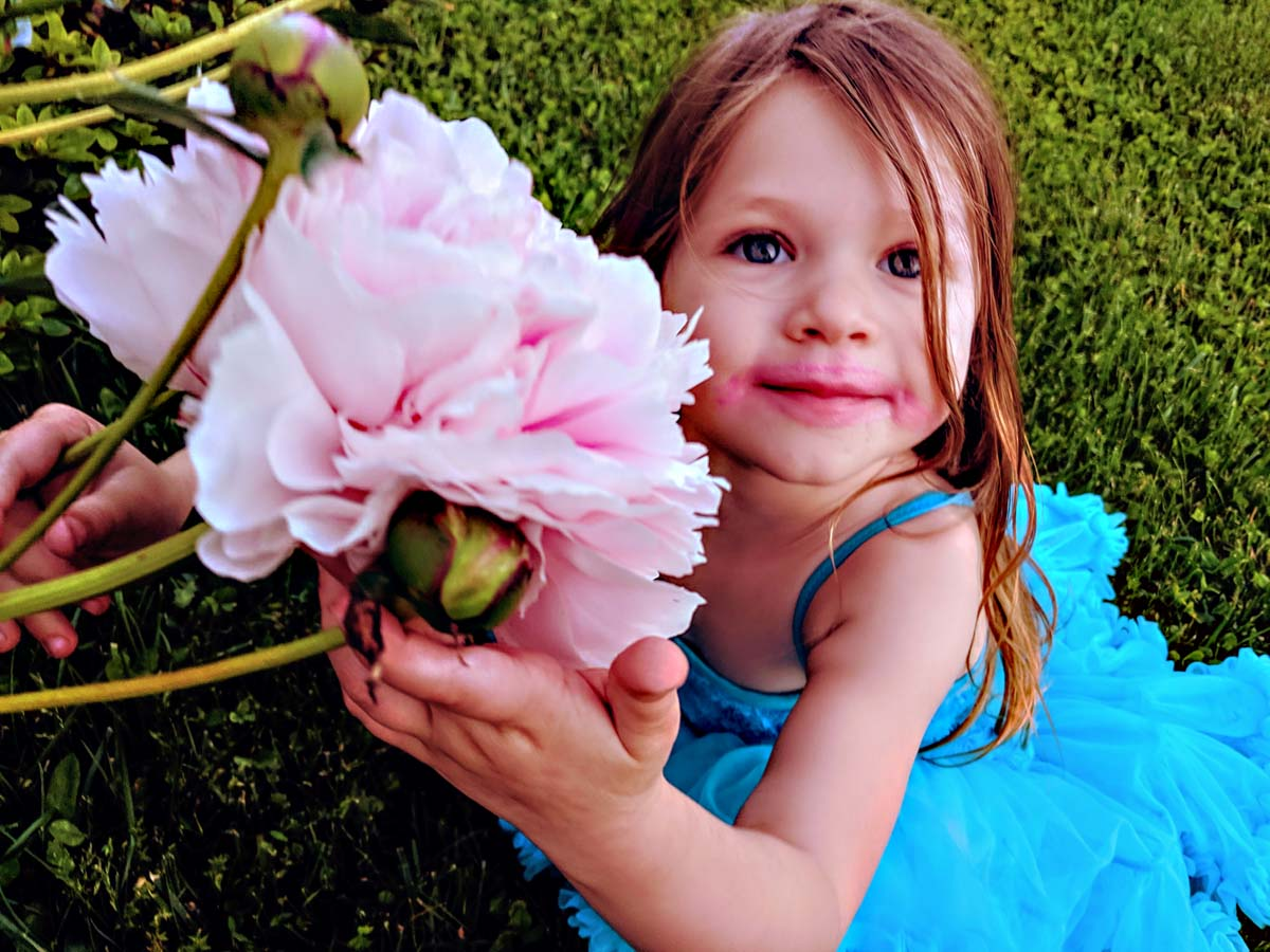 Daughter Holding Pink Fluffy Peony Flower in Garden in Blue Dress