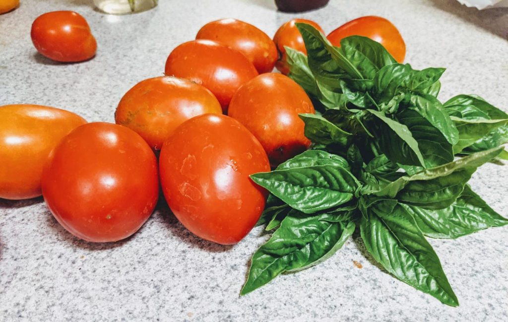 Basil and Tomatoes go well together! Pile of Roma tomatoes with fresh basil leaves on the counter
