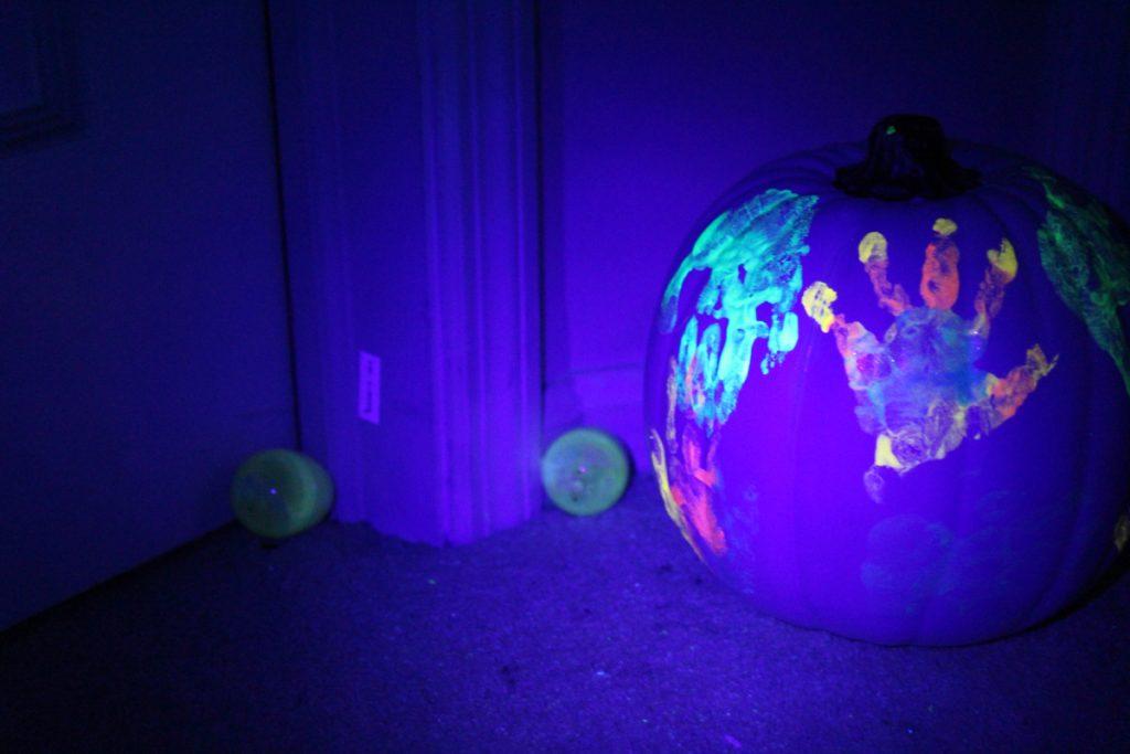 Glowing Halloween Handprints on a White Faux Pumpkin Preschool Halloween Craft